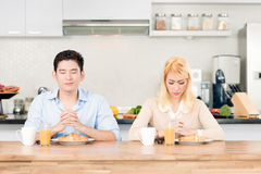 Couple praying before having breakfast together Stock Images