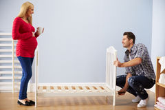 Couple With Pregnant Wife Assembling Cot In Nursery royalty free stock photos