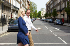 Couple With Pregnant Wife Crossing City Road Royalty Free Stock Photography