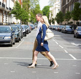 Couple With Pregnant Wife Crossing City Road. Looking Away From Camera stock image