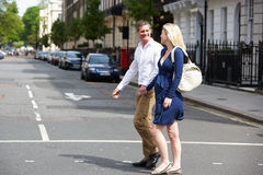 Couple With Pregnant Wife Crossing City Road Stock Images