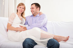Couple With Pregnant Woman Relaxing On Sofa Together Stock Images