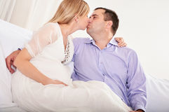 Couple With Pregnant Woman Relaxing On Sofa Together Stock Photos