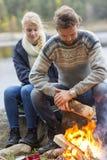 Couple Preparing Bonfire During Lakeside Camping Stock Photography