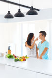 Couple preparing dinner. Woman is touching man's nose stock photos