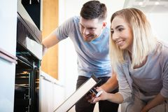 Couple preparing food. Happy lifestyle concept - smiling young couple preparing food at home while looking into the oven royalty free stock images