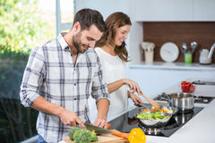 Couple preparing food at kitchen counter Stock Image