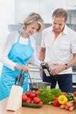 Couple preparing food in kitchen. Man Looking At Woman Preparing Food In Kitchen stock photo