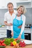 Couple Preparing Food In Kitchen. Man Looking At Woman Preparing Food In Kitchen stock photography