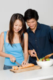 Couple Preparing Meal. A good looking couple preparing a meal of bread and salad in the kitchen at home stock photos
