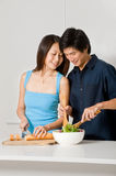 Couple Preparing Meal. A good looking couple preparing a meal of bread and salad in the kitchen at home royalty free stock photos