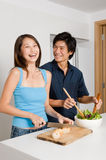 Couple Preparing Meal. A good looking couple preparing a meal of bread and salad in the kitchen at home royalty free stock images