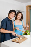 Couple Preparing Meal. A good looking couple preparing a meal of bread and salad in the kitchen at home stock image