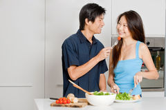 Couple Preparing Meal. A good looking couple preparing a meal of bread and salad in the kitchen at home stock images