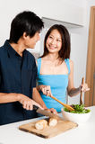Couple Preparing Meal. A good looking couple preparing a meal of bread and salad in the kitchen at home royalty free stock image