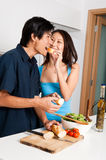 Couple Preparing Meal. A good looking couple preparing a meal of bread and salad in the kitchen at home stock photo