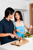 Couple Preparing Meal. A good looking couple preparing a meal of bread and salad in the kitchen at home royalty free stock photo