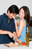 Couple Preparing Meal. A good looking couple preparing a meal of bread and salad in the kitchen at home stock photography