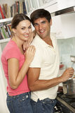 Couple Preparing Meal At Cooker Royalty Free Stock Photos