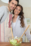 Couple preparing meal in kitchen Stock Photos