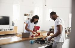 Couple Preparing Meal Together In Modern Kitchen Royalty Free Stock Image