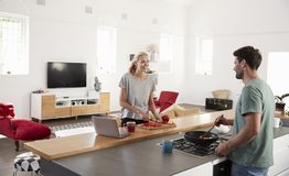 Couple Preparing Meal Together In Modern Kitchen Royalty Free Stock Images