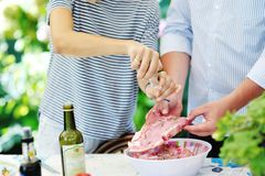 Couple preparing meat to cook on the barbecue Stock Images
