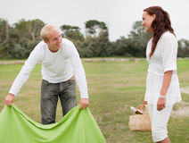 Couple preparing romantic picnic. On a meadow Stock Images