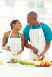 Couple preparing salad. Loving afro american couple preparing green salad in kitchen Royalty Free Stock Photo