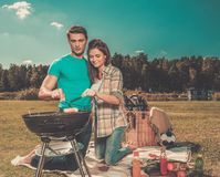 Couple preparing sausages outdoors Royalty Free Stock Images