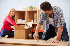 Couple Preparing To Assemble Flat Pack Furniture In Nursery Royalty Free Stock Photography