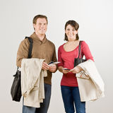 Couple preparing to travel with airline tickets. Busy couple preparing to travel with airline tickets, coats and briefcase Stock Photos
