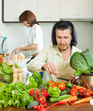 The couple preparing vegetable salad Stock Images