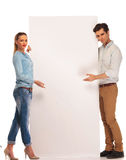 Couple presenting a white blank billboard Stock Image