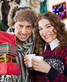 Couple With Presents And Coffee At Christmas Store Stock Image