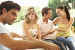Couple With Problems Amongst Group Of Friends Relaxing On Sofa Stock Photos