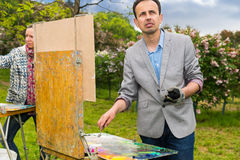 Couple of professional contemplative middle-aged  painters worki Stock Photos