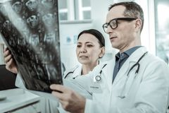 Couple of professional doctors attentively reviewing x-ray photo. Workmate interestedly looking. Couple of professional doctors attentively reviewing x-ray photo stock images