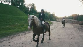 Couple of proffesional jockeys man and woman are riding horses at the countryside road.  stock video