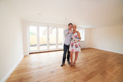 Couple With Property Details Looking Around New Home Stock Photo