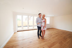 Couple With Property Details Looking Around New Home Stock Photos
