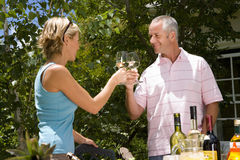 Couple proposing toast with wine glasses in garden, low angle view Royalty Free Stock Image