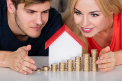 Couple Protecting House Model With Stacked Coins Stock Image
