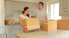 Couple proudly put moving boxes in the kitchen Royalty Free Stock Image