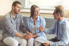 Couple at the psychotherapist. Young couple is holding hands while sitting on the couch at the psychotherapist. Handsome middle aged doctor is holding a folder Stock Photography