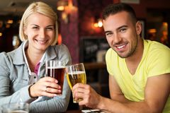 Couple in a pub. Beautiful couple enjoying beer in a pub royalty free stock photo