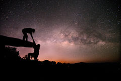 Couple pull each other on Stone lodge under night sky stars Stock Photography