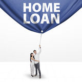 Couple pulling a home loan banner. Portrait of asian couple pulling a home loan banner in studio, isolated over white background Royalty Free Stock Photography