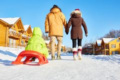 Outdoor family weekend. Couple pulling sled with their little son while walking along snowy path in countryside on sunny winter afternoon, rear low angle view Stock Images