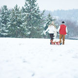 Couple pulling sled in winter Royalty Free Stock Photos